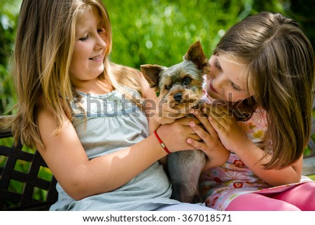 Happy smiling children playing with their pet - outdoor in backyard - stock photo