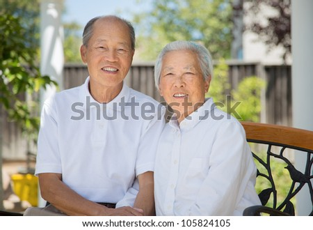 Happy Smiling Chinese Elderly Sitting on Garden Chair Backyard - stock photo