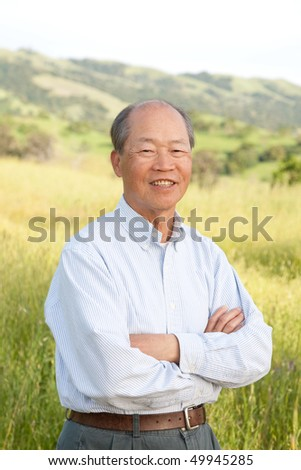 Happy Smiling Chinese Elderly Standing in front of Farmland - stock photo