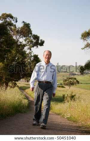 Happy Smiling Chinese Elderly Walking in Outdoor Park