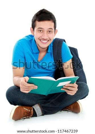 Happy smiling college student sit on the floor reading a book - stock photo
