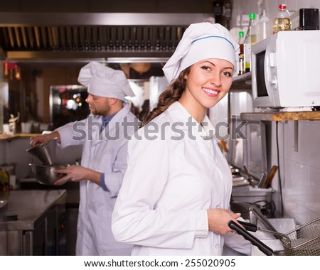 Happy smiling cooks working together at kitchen in take-away restaurant