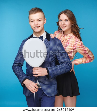 Happy smiling couple boy and beautiful holding white balloon on blue background. Hipster style. - stock photo