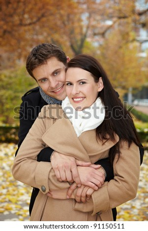 Happy smiling couple embracing in a fall park - stock photo