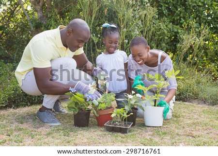 Happy smiling couple gardening with their daughter at home in garden