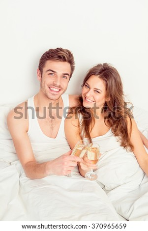 Happy smiling couple in love at home embracing each other with champagne - stock photo