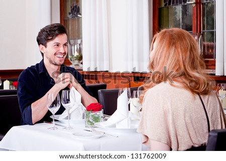happy smiling couple in restaurant for dinner sitting talking drinking