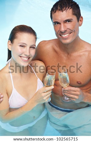 Happy smiling couple in swimming pool drinking sparkling wine - stock photo