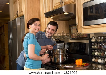Happy, smiling couple in the kitchen near a counter, microwave, and a chopped pepper. He is about to taste the food she is cooking on the stove.  Horizontally framed photograph - stock photo