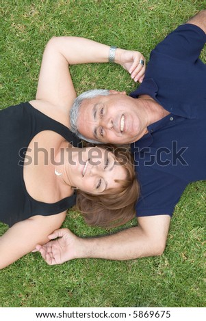 Happy smiling couple in their fifties together outdoors - stock photo
