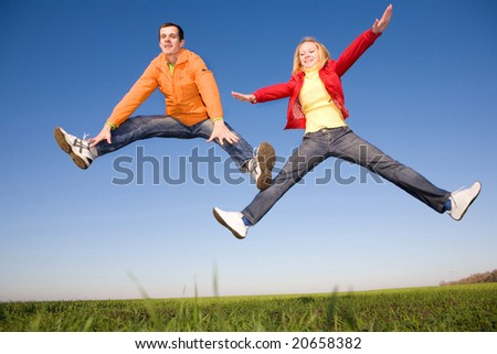 Happy smiling couple  jumping in sky
