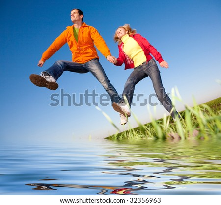 Happy smiling couple  jumping in sky above a green meadow. Reflected in Water. - stock photo