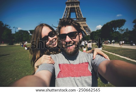 Happy smiling couple kissing and taking selfie photo in front of Eiffel Tower in Paris while traveling across France - stock photo