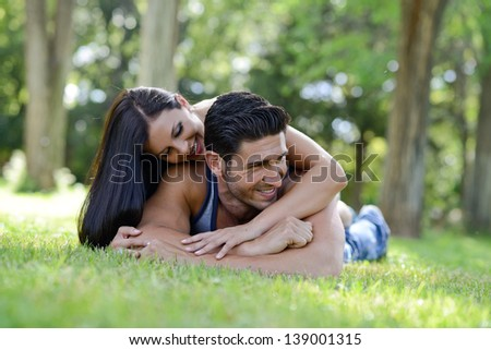 Happy smiling couple laying on green grass in a beautiful park - stock photo