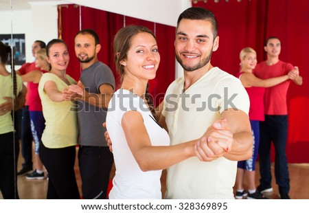 Happy smiling couple learning to dance waltz in dancing school with other dancing pairs in background - stock photo