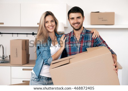 Happy smiling couple looking at camera while holding box with belongings in kitchen