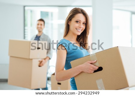 Happy smiling couple moving in a new house and carrying carton boxes, relocation and renovation concept - stock photo