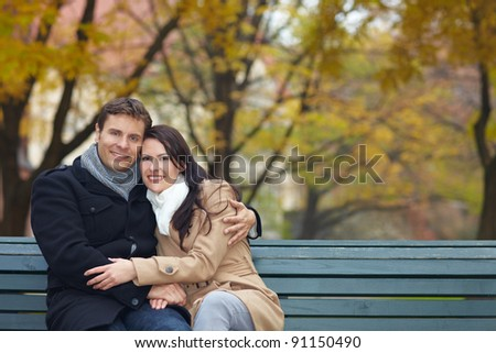 Happy smiling couple on park bench in fall - stock photo