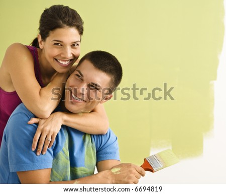 Happy smiling couple painting interior wall of home. - stock photo