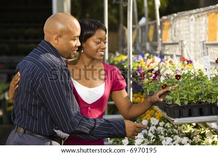 Happy smiling couple picking out flowers at outdoor plant market. - stock photo