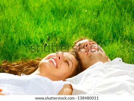 Happy Smiling Couple Relaxing on Green Grass. Park. Young Couple Lying on Grass Outdoor - stock photo
