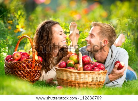 Happy Smiling Couple Relaxing on the Grass and Eating Apples in Autumn Garden.Healthy Food.Outdoor.Park.Basket of Apples.Harvest concept - stock photo