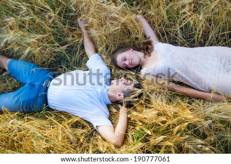happy smiling couple relaxing on wheat field  Young couple lying on grass outdoor - stock photo