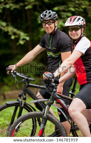Happy smiling couple riding bicycles in the park
