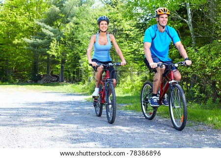 Happy smiling couple  riding  in the park - stock photo