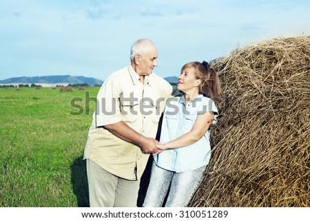happy smiling couple: sixty eight year old man and sixty five year old woman isolated against blue background - stock photo