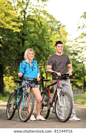 Happy smiling couple with bikes posing in the park - stock photo