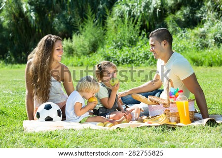 Happy smiling couple with little daughters having holiday with picnic at park - stock photo