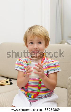 happy smiling cute blond child drink a glass of milk sitting sofa in the living room