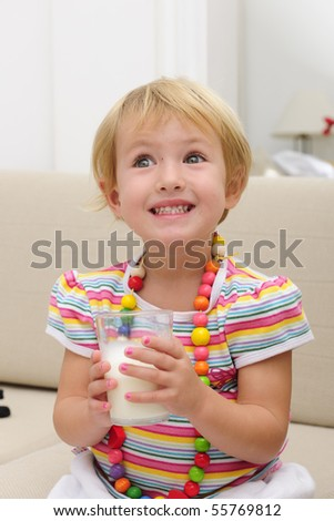 happy smiling cute blond child drink a glass of milk sitting sofa in the living room - stock photo