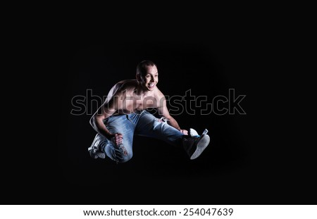 happy smiling dancer jumping on a black background - stock photo