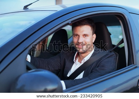 happy smiling driver in the car, portrait of young successful business man - stock photo