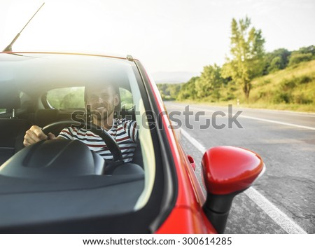 Happy smiling driver man in new red car on the road. Toned photo. - stock photo