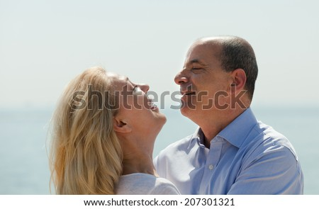 Happy smiling elderly couple hugging with love at sea shore in warm season - stock photo