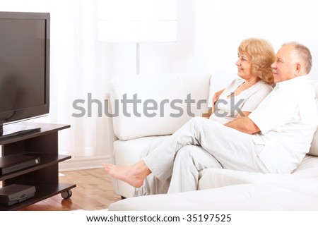 Happy smiling elderly couple watching TV at home - stock photo