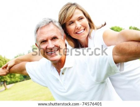Happy smiling elderly seniors couple in park. - stock photo