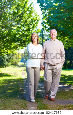 Happy smiling elderly seniors couple in park. - stock photo
