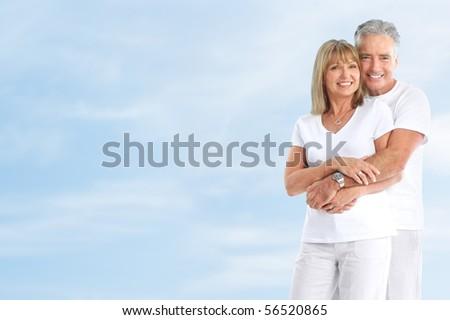 Happy smiling elderly seniors couple under blue sky - stock photo