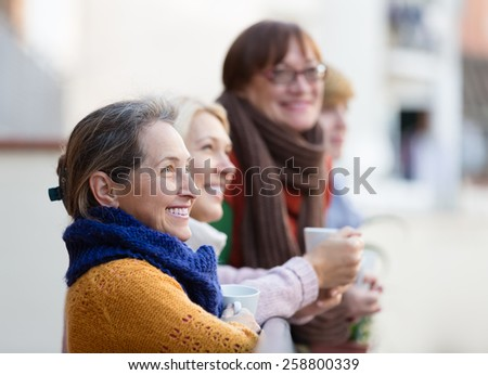 Happy smiling elderly women drinking coffee at patio - stock photo