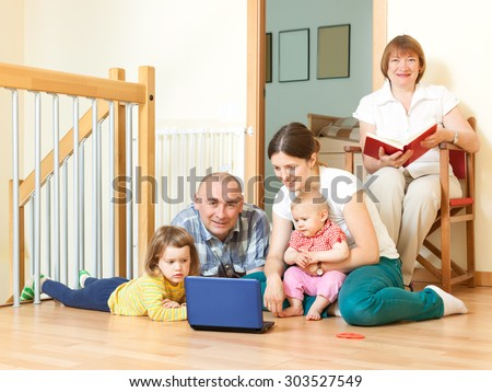 Happy smiling family enjoys on floor with laptop  in livingroom at home interior   - stock photo