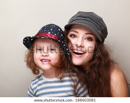 Happy smiling family in trendy caps. Loving mother and daughter. Closeup - stock photo