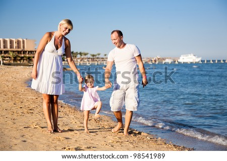 Happy smiling family: man, women and kid playing at the sea beach. Summer vacations concept