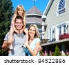 Happy smiling family near new house. Realty. - stock photo