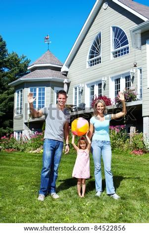 Happy smiling family near new house. Realty. - stock photo