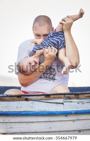 Happy smiling family of bold fat father and cute little infant baby on a seashore near nature in blue, white and red outfit: t-shirt and shorts. Summer day - stock photo