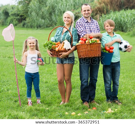 Happy smiling family of four having rest at countryside at summer day